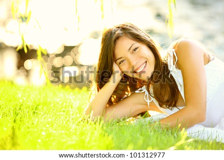 Summer girl in grass smiling happy. Lifestyle image of beautiful young woman in summer dress lying joyful in park on sunny sunshine day. Mixed race Caucasian / Asian Chinese female model. - stock photo