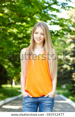 Summer girl portrait.  Casual woman standing with hands in pockets smiling happy on sunny summer or spring day outside in park. Pretty young woman outdoors. - stock photo