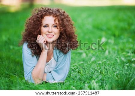 Summer girl portrait, smiling girl in green grass - stock photo