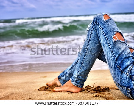Summer girl sea.  Woman sitting on coast near ocean with waves. Hot dog leg wearing jeans with holes selfie.  - stock photo
