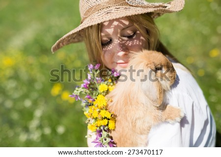 summer girl with bunny in the nature, selective focus on the bunny - stock photo