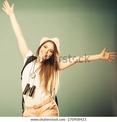 Summer happiness and tourism concept. Young woman in straw hat with backpack spreading hands with joy, happy successful girl with arms up - stock photo