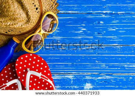 Summer holiday background, Beach accessories on white wood table, Vacation and travel items, Red flip flop with sunglasses, moisturizer and straw hat on wood table - stock photo