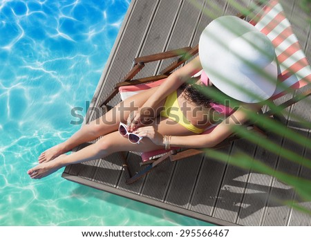 Summer holiday fashion concept - tanning woman wearing sun hat on a wooden beach chair at the pool view from above - stock photo
