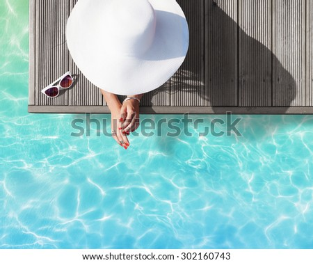 Summer holiday fashion concept - tanning woman wearing sun hat on a wooden pier view from above - stock photo