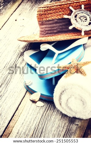 Summer holiday setting with flip flops and straw hat - stock photo