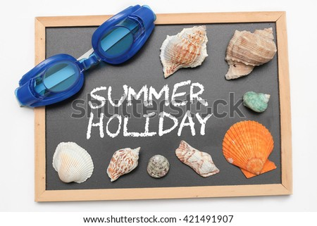 Summer Holiday text on chalk board with swimming goggle and shell - vacation and business concept - stock photo