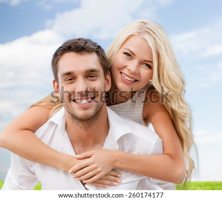summer holiday, vacation, dating and love concept - happy couple having fun over blue sky and grass background - stock photo