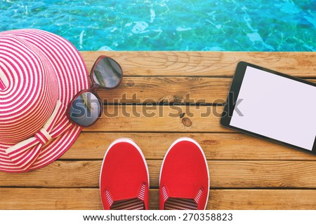 Summer holiday vacation essential objects on wooden deck. View from above - stock photo