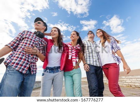 summer holidays and teenage concept - group of smiling teenagers in sunglasses hanging outside - stock photo