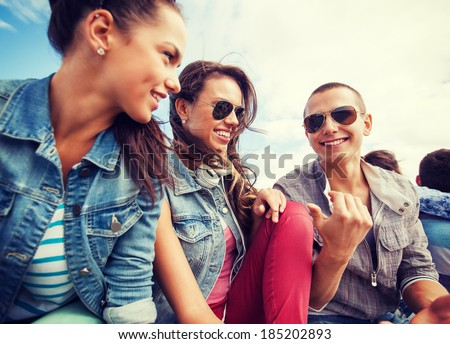 summer holidays and teenage concept - group of teenagers hanging out outside - stock photo