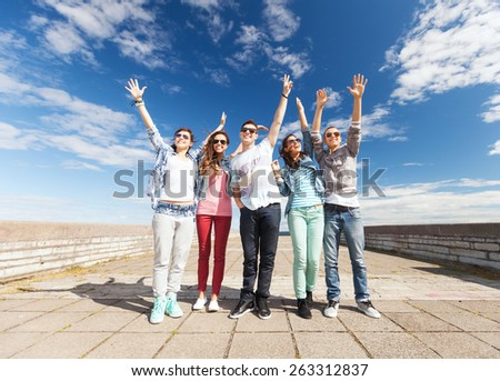 summer holidays and teenage concept - group of teenagers holding hands up outside - stock photo