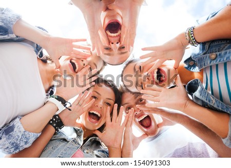 summer holidays and teenage concept - group of teenagers looking down and screaming - stock photo