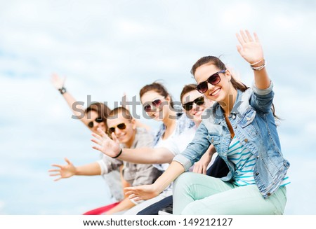 summer holidays and teenage concept - group of teenagers waving hands - stock photo