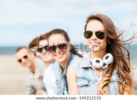 summer holidays and teenage concept - teenage girl with friends outside - stock photo