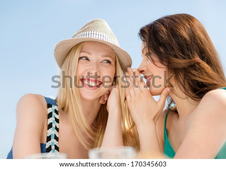 summer holidays and vacation concept - girls gossiping in cafe on the beach - stock photo
