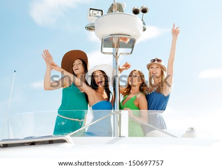 summer holidays and vacation concept - girls waving on boat or yacht - stock photo