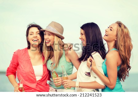 summer holidays and vacation concept - smiling girls with drinks on the beach - stock photo