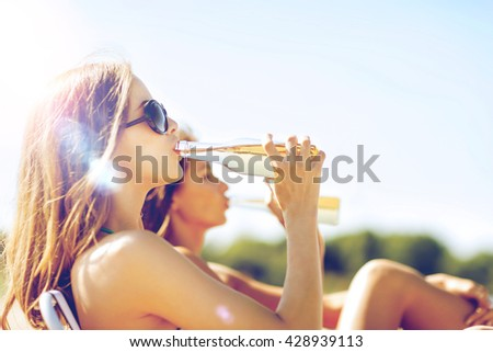 summer holidays and vacation - girls in bikinis with drinks on the beach chairs - stock photo