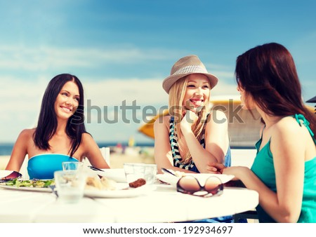 summer holidays and vacation - girls in cafe on the beach - stock photo