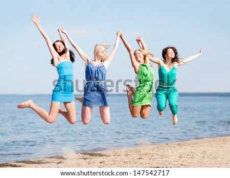 summer holidays and vacation - girls jumping on the beach - stock photo