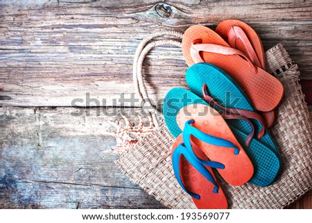 Summer holidays bag, sun glasses and flip flops on wooden background - stock photo