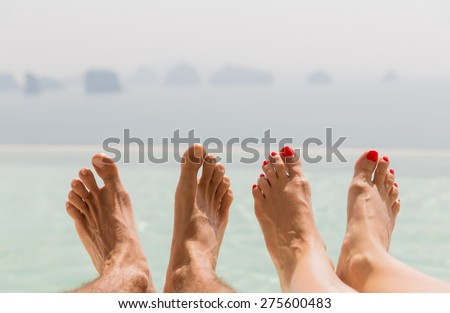 summer holidays, beach, travel, leisure and body care concept - closeup of couple feet over sea and sky on beach - stock photo