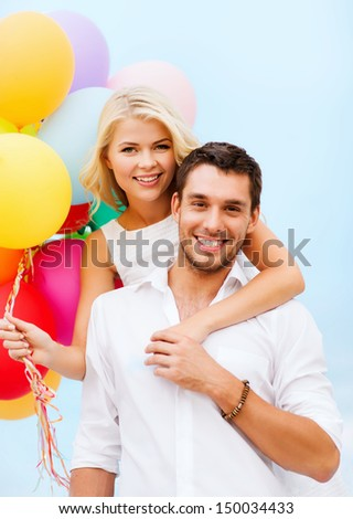 summer holidays, celebration and dating concept - couple with colorful balloons at seaside - stock photo