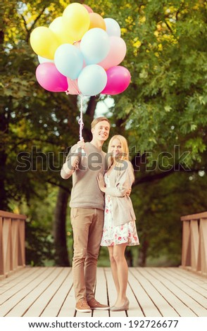 summer holidays, celebration and dating concept - couple with colorful balloons in the park - stock photo