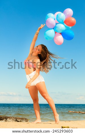 Summer holidays, celebration and lifestyle concept - attractive athletic woman teen girl with colorful balloons outside on beach seashore background - stock photo