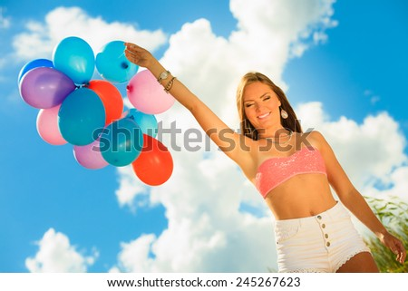 Summer holidays, celebration and lifestyle concept - attractive woman teen girl with colorful balloons outside on beach blue sky background - stock photo