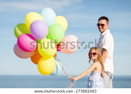 summer holidays, celebration, children and family concept - happy father and daughter with colorful balloons at seaside - stock photo