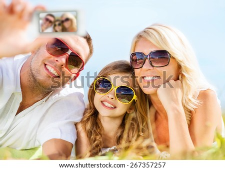 summer holidays, children and people concept - happy family with camera, blue sky and green grass taking picture - stock photo