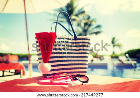 summer holidays, christmas and vacation concept - santa helper hat, bag, sunscreen and sunglasses - stock photo