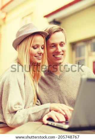 summer holidays, city, dating and technology concept - smiling couple with laptop computer in cafe - stock photo