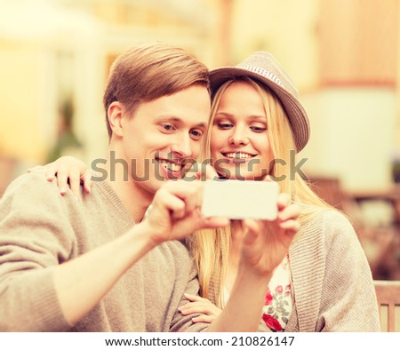 summer holidays, dating and technology concept - couple taking selfie with smartphone at cafe in the city - stock photo