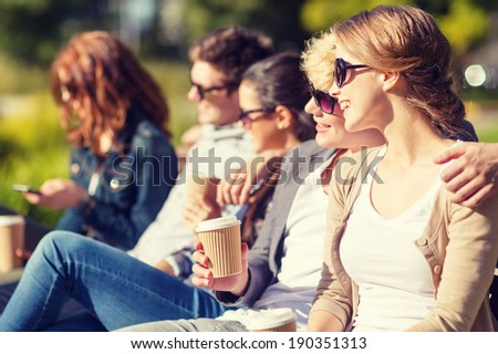 summer holidays, education, campus and teenage concept - group of students or teenagers with takeaway coffee cups hanging out - stock photo