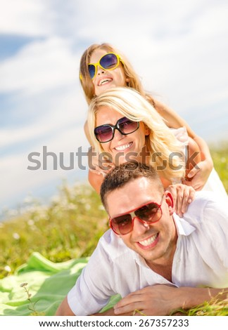 summer holidays, family, child and happy people concept - smiling family in sunglasses lying on blanket outdoors - stock photo