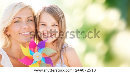 summer holidays, family, children and people concept - happy mother and girl with pinwheel toy over green background - stock photo