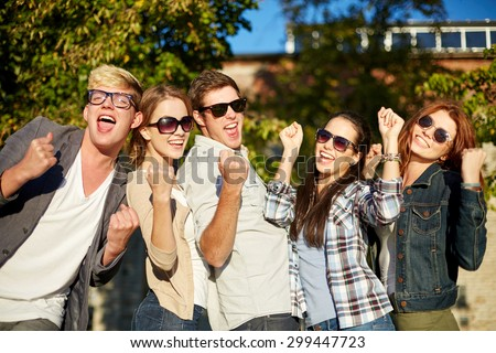 summer holidays, friendship, achievement and success concept - group of happy friends showing triumph gesture at campus or city park - stock photo