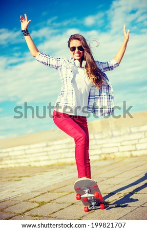 summer holidays, leisure and teenage concept - smiling teenage girl in sunglasses riding skate outside - stock photo