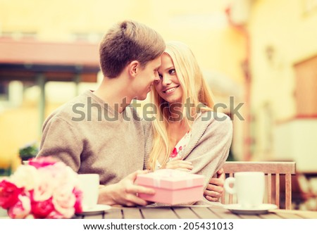 summer holidays, love, travel, tourism, relationship and dating concept - romantic happy couple with gift in the cafe - stock photo