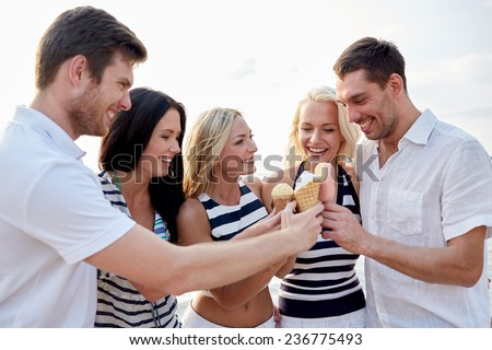 summer, holidays, sea, tourism and people concept - group of smiling friends eating ice cream on beach - stock photo