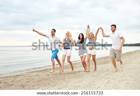 summer, holidays, sea, tourism and people concept - group of smiling friends in sunglasses running on beach - stock photo