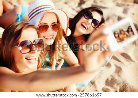summer holidays, technology and beach concept - girls making self portrait on the beach - stock photo