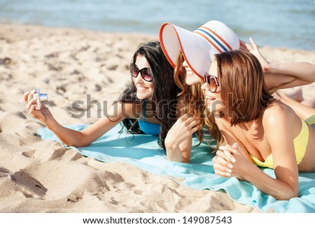 summer holidays, technology and beach concept - girls taking selfie on the beach - stock photo