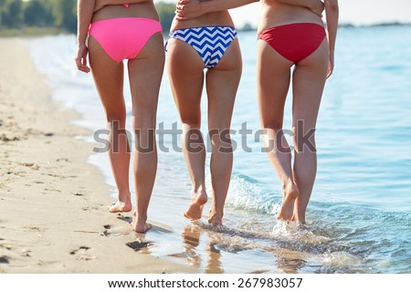 summer holidays, travel, body care and people concept - close up of happy young women walking and hugging on beach from back - stock photo