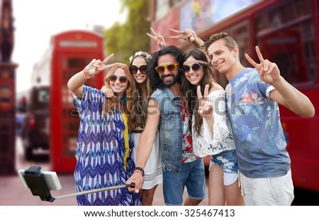 summer holidays, travel, technology and people concept - smiling young hippie friends taking picture by smartphone on selfie stick and showing peace gesture over london city street background - stock photo