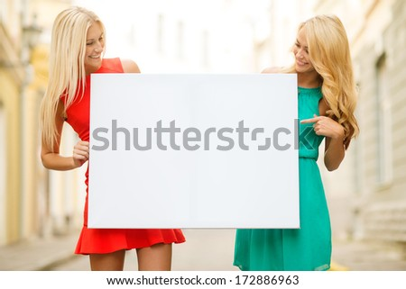 summer holidays, , travel, tourism and advertisement concept - two happy blonde women with blank white board in the city - stock photo