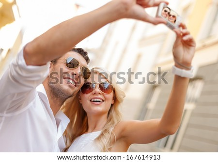 summer holidays, travel, vacation, tourism and dating concept - travelling couple taking photo picture with camera - stock photo